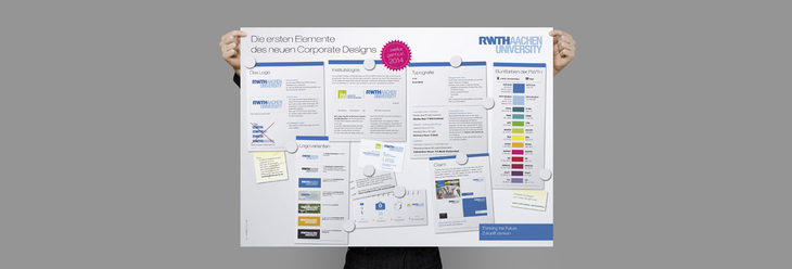 Someone holds a poster with details about RWTH's new Corporate Design