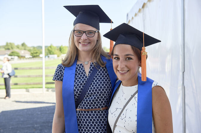 Two graduates smiling into the camera